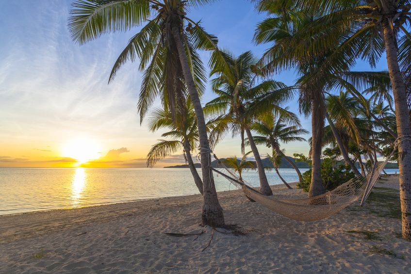19254387 - tropical paradise beach at sunset with hammock